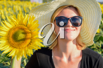 Girl on the field of sunflowers. Girl with sunglasses and a white hat. The sunflower blooms.