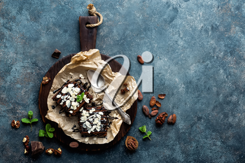 Chocolate brownie cake, dessert with nuts on dark background, directly above, copy space, flat lay