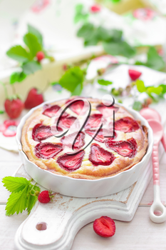 Delicious strawberry tart or cheesecake with fresh berries and cream cheese, closeup on white wooden rustic background