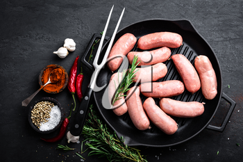 Fresh raw sausages on a cast-iron grill pan on a black background, top view