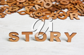 Word Story made with wooden letters on a background of other blurred letters
