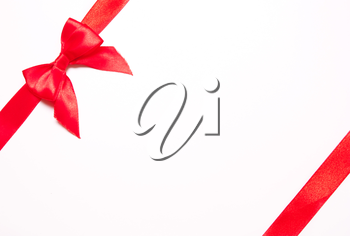Red ribbons with bow with tails  on white background. The concept of gift, holiday