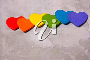 Wooden hearts of the color of the rainbow on a gray background. symbol of LGBT