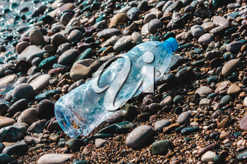Plastic bottle on the beach, on the beach. Concept of pollution of the environment, ocean, sea, nature. Save the planet.