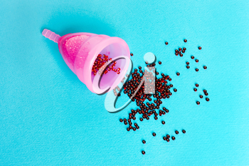 pink menstrual cup  with a drop of blood on a blue background. Concept of women's health, hygienic means of protection, menstruation, ecology of the planet.