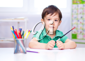 Little boy is drawing on white paper using color pencils