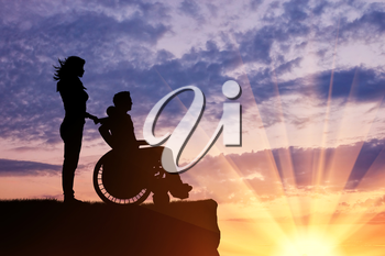 Concept of disability and disease. Silhouette of disabled person with a guardian on the hill in the evening