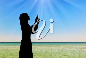 Concept of Islamic culture. Silhouette of praying woman against the sea in the rays