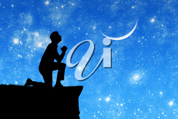 Concept of religion. Silhouette of man praying on the background of the sky with the moon and stars