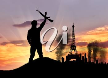 Concept of terrorism. Silhouette of the terrorist and the city in smoke against the sunset
