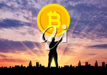 Silhouette of a man holding a coin bitcoin against the background of the city at sunset. The concept of the future for crypto currency