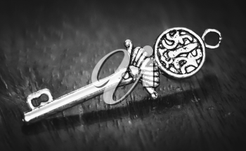 Beautiful silver key on a wooden background. Photo tinted.