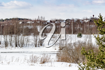 A beautiful March landscape with a village in the background and a frozen river.