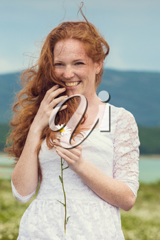 Beautiful young girl with curly red hair in camomile field