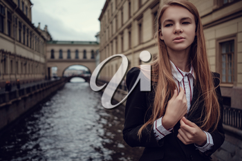 A young red-haired girl in a business suit is walking along a beautiful old town. St.Petersburg