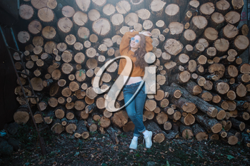 beautiful amazing gorgeous redhair girl spins in yellow sweater, jeans and glasses on the background of firewood. Autumn mood