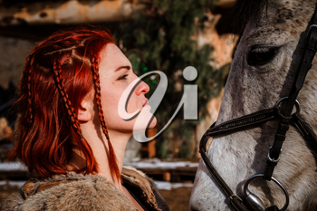 Red-haired woman with a faithful horse preparing for battle