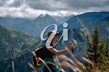 A young woman with a backpack and a tracking stick is climbing a mountain. Tatra National Park, Poland