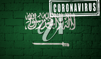Flag of the Saudi Arabia with original proportions. stamped of Coronavirus. brick wall texture. Corona virus concept. On the verge of a COVID-19 or 2019-nCoV Pandemic.