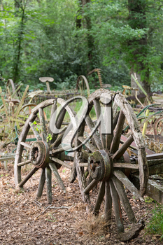 Pair of old wooden cartwheels against a ruined wood cart or buggy in farm forest