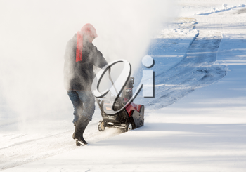Senior lady using a snowblower on rural drive on windy day with a cloud or blizzard of snow blowing in the air