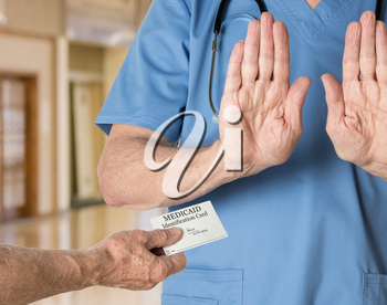 Senior caucasian doctor in scrubs in hospital refusing to treat a patient with a Medicaid card