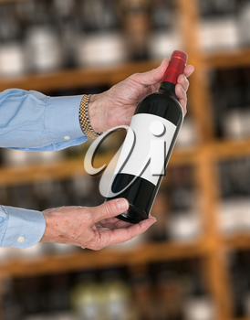 Senior caucasian wine steward offering a bottle of red wine with blank label to a customer in a wine store or winery. The bottle is ready with copy space.