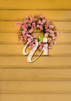 Pink wreath with flowers and ribbon and small bunny rabbit shape for easter celebrations