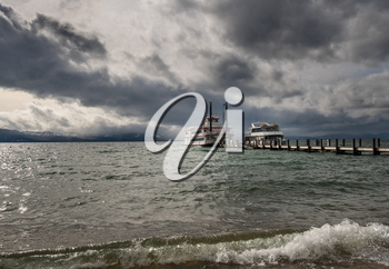 Cruise boats wait for passengers on Lake Tahoe in stormy spring day with snow on the distant Sierra Nevada Mountains