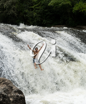 CASHIERS, NORTH CAROLINA - AUGUST 21, 2016: Young adult slides down rocks in Turtleback Falls in Gorges State Park near Cashiers in North Carolina, USA