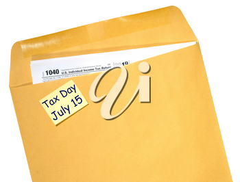 Printed Form 1040 for income tax return in brown envelope with reminder for July 15 tax day due to Covid-19 virus delay