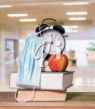 Concept for back to school with coronavirus or Covid-19 with books, alarm clock and apple with face mask against background of school corridor