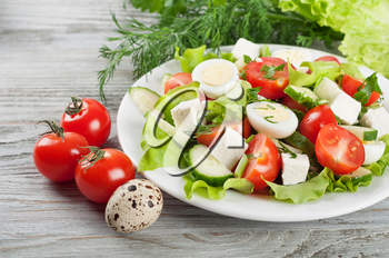 Fresh salad with quail eggs, cherry tomato, cucumber and lettuce on a wooden background