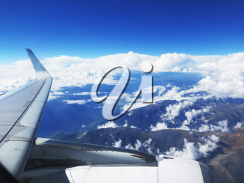 Wing of the plane on blue sky and clouds background