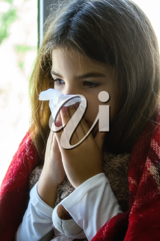 a sick little girl sits at the window wrapped in a blanket and blows her nose into a disposable napkin