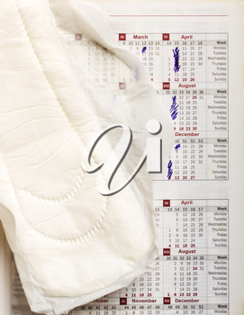 Hygienic liner lying over the calendar with marked days when menstrual cycles