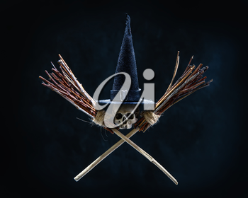 Halloween image Skull in a traditional witch pointed black hat and two crossed brooms on an ominous dark background