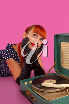 Pin-up model girl in retro polka-dot dress listens to an old gramophone on a pink background