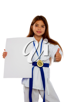 karate girl with a blue belt and a white kimono and a medal for first place holds a blank sheet of paper in her hands with a place for text.
