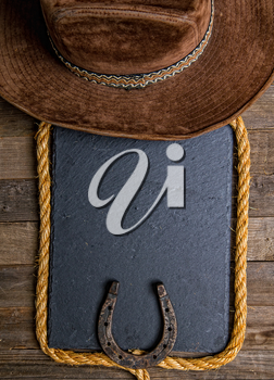 Black chalk board lasso horseshoe and traditional cowboy hat on wooden background