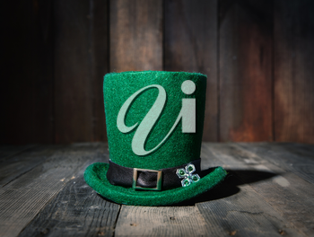 green classic leprechaun bowler hat on old wooden table in a pub