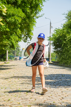 little girl athlete goes to martial arts training on an empty street with a backpack with equipment