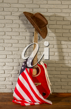 a traditional wide-brimmed cowboy hat, and the Stars and Stripes USA flag hang on a classic acoustic guitar