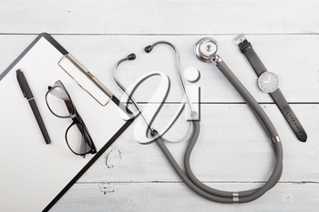 Workplace of doctor - stethoscope, medicine clipboard, glasses and watches on wooden desk