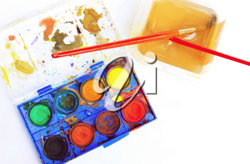 Top down view of old used watercolor palette box with paint brushes in cup with water on white paper.