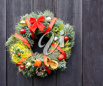 Christmas handmade decorative wreath with small ornaments and red ribbons on wooden background.