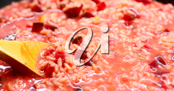 Close-up of an Italian Creamy Beetroot Risotto and Stirring Wooden Spoon.