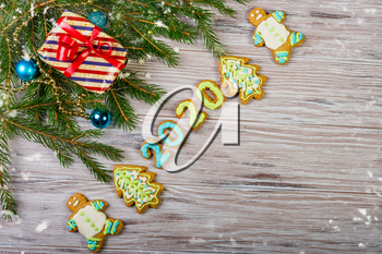 Glazed Christmas gingerbread and Christmas tree branches on a wooden background