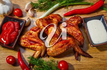 Fried chicken wings and vegetables on a wooden background