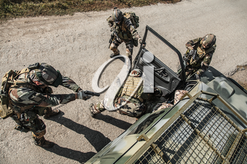 Squad of elite french paratroopers of 1st Marine Infantry Parachute Regiment RPIMA detaining terrorist in the car, top view from above